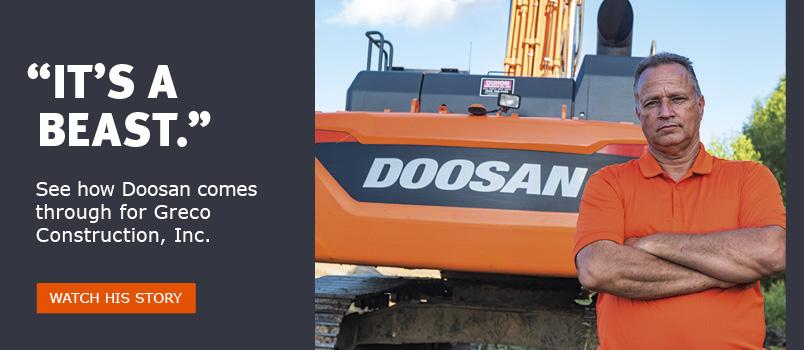 Lane Greco standing in front of his Doosan excavator