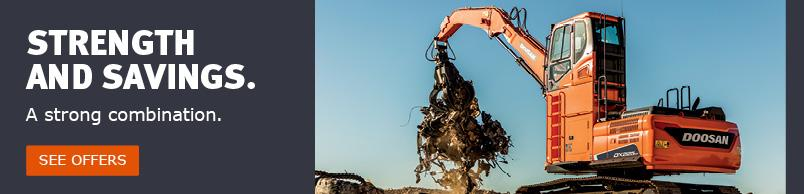 Doosan material handler lifting a mix of debris and discarded rubber tracks.